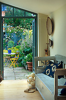 A Swedish-style wooden bench in the conservatory has a view of the garden through open French windows