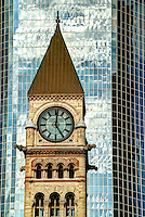 Close-up view of the clock tower of Old City Hall in front of a downtown Toronto modern glass skyscraper, Toronto, Ontario, Canada