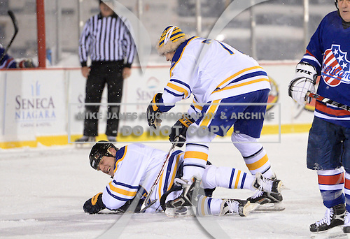 Andrew Peters (76) stands over Rob Ray (32) after knocking him down during The Frozen Frontier Buffalo Sabres vs. Rochester Amerks Alumni Game at Frontier Field on December 15, 2013 in Rochester, New York.  (Copyright Mike Janes Photography)
