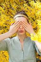 Young woman covering her eyes standing amoungst Forsythia flowers