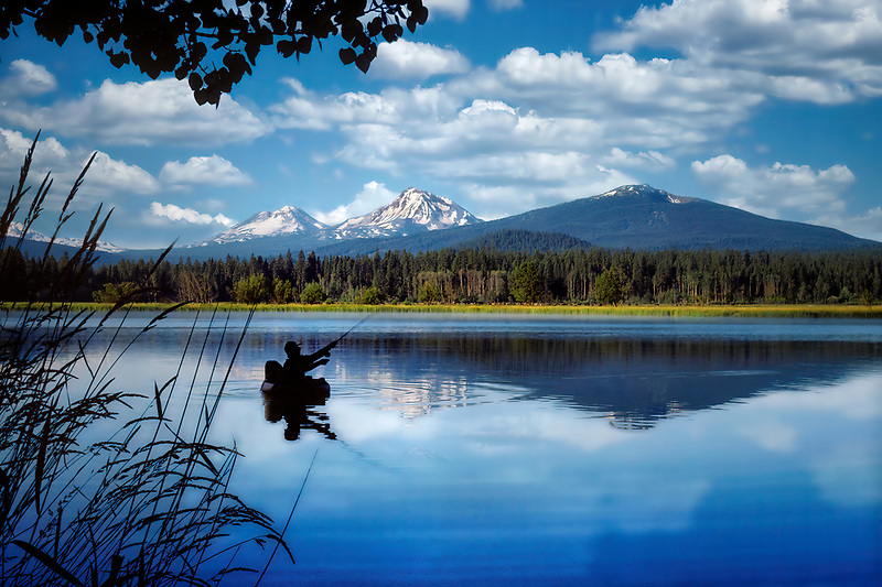 Float tube fly fisherman on Black Butte pond with Three Sisters Mountains. Oregon.