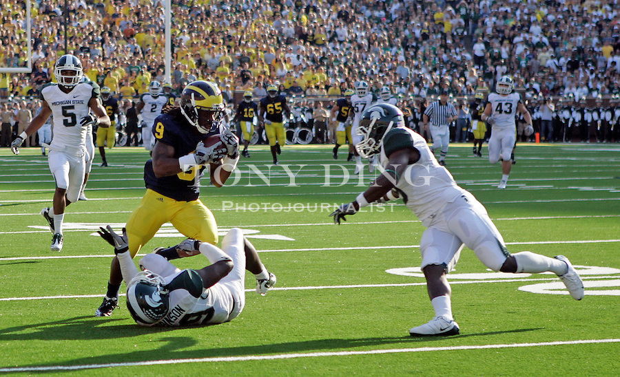 Michigan wide receiver Martavious Odoms (9) makes a 51-yard catch, defended by Michigan State safety Trenton Robinson, bottom, and safety Isaiah Lewis, right, in the second quarter of an NCAA college football game, Saturday, Oct. 9, 2010, in Ann Arbor, Mich. (AP Photo/Tony Ding)