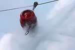 A red barrel on a tether line pushed by fire hoses and water spray in a form of a firefighter tug of war