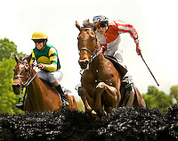 Two jockey's compete for position as they jump over a hurdle during the Queen's Cup Steeplechase in Mineral Springs, NC.