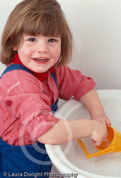 """portrait of 2 year old toddler girl happy at sink pretend play """"washing"""" plastic toy dishes Caucasian vertical"""