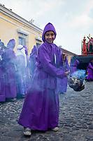 Antigua, Guatemala.  Boy Swings an Incense Pot as he Precedes a Religious Procession during Holy Weekj, La Semana Santa.