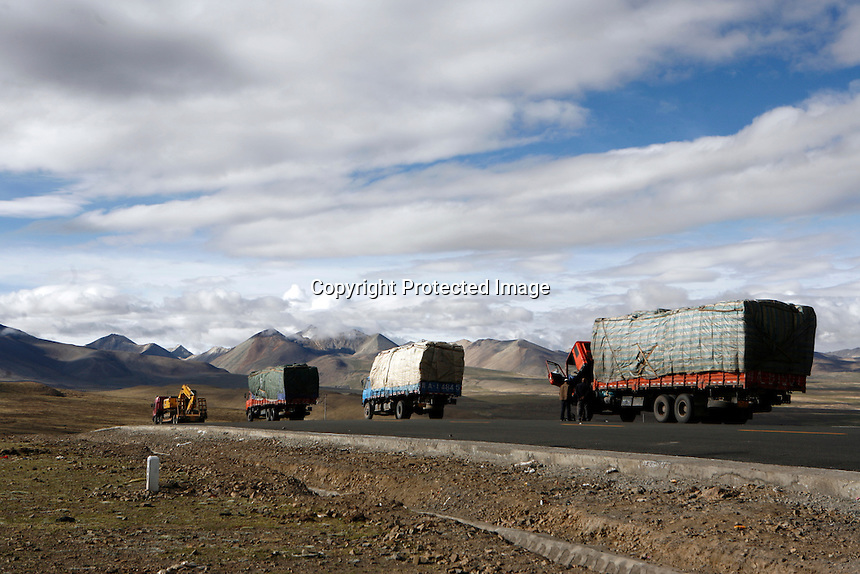 "Trucks roll down the Friendship Highway between Lhasa and Nepal.<br /> China started building a controversial 67-mile ""paved highway fenced with undulating guardrails"" to Mount Qomolangma, known in the west as Mount Everest, to help facilitate next year's Olympic Games torch relay. <br /> Tibet, China.<br /> July, 2007"