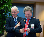 John Rotz helps newly minted Hall of Famer Don Pierce put on his members-only jacket.