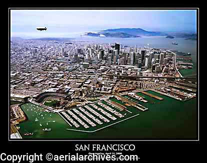 """This 22"""" x 28"""" aerial poster of San Francisco is a view created on the very first Opening Day, April 11, 2000 at San Francisco's baseball stadium, ATT park, also once known as SBC park and PacBell park, home of the San Francisco Giants. <br /> <br /> San Francisco Giants' baseball park in San Francisco is the first privately financed stadium in major league baseball since Dodger Stadium in 1962. With a seating capacity of 41,503 the park has a unique setting at the edge of San Francisco bay, with outstanding seats--the first row of seats is only 48 feet from homeplate.<br /> <br /> The Goodyear blimp was flying and broadcasting overhead on this day. The poster also shows a containership emerging from the fog entering San Francisco bay beneath the Golden Gate bridge, an audience of boats in McCovey Cove adjacent to the ballpark, and provides an excellent view of San Francisco's South Beach marina."""