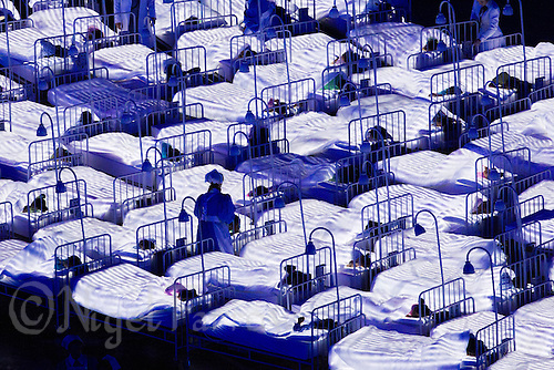 """27 JUL 2012 - LONDON, GBR - A nurse walks between the beds of sleeping children during the """"Second To The Right, And Straight On Till Morning"""" section of the Opening Ceremony of the London 2012 Olympic Games in the Olympic Stadium in the Olympic Park, Stratford, London, Great Britain (PHOTO (C) 2012 NIGEL FARROW)"""