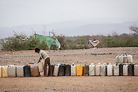 Tuesday 07 July, 2015: Containers are seen queueing as a displaced child from the heavy fighting in Haradh bordertown await for water distribution in a temporary settlement at the outskirts of Beni Hassan in Hajjah province, Northwest of Yemen. (Photo/Narciso Contreras)
