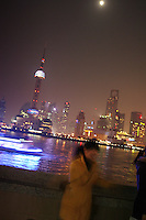 CHINA. Shanghai. A tourist on the Bund with the famour PuDong skyline behind her.  Shanghai is a sprawling metropolis or 15 million people situated in south-east China. It is regarded as the country's showcase in development and modernity in modern China. This rapid development and modernization, never seen before on such a scale has however spawned countless environmental and social problems. 2008.