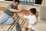 Father with an interest in World War II airplanes and battleships playing with his 6 year old son, who shares his passion