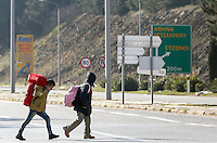 Pictured: Two migrant children walk on the main road Tuesday 23 February 2016<br /> Re: Migrants trying to cross the Greek-FYRO Macedonian border, were turned away by the authorities in Idomeni, Greece.