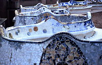 Mosaic details in serpentine wall in Parc Guell, designed by Antoni Gaudi. Barcelona, Spain.