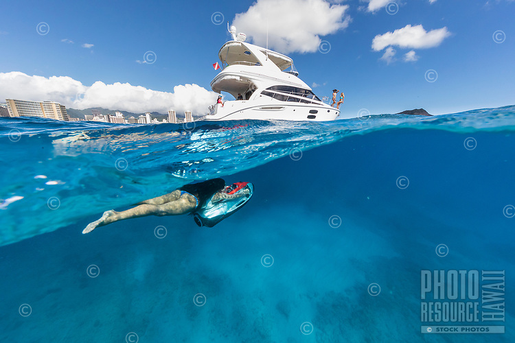 A woman rides an underwater sled towards a power cruiser off of Waikiki, O'ahu.