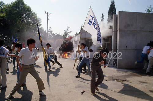 """Seoul, South Korea.June 9, 1987..Students hold a violent anti-government protests at Yunsei University. A tear gas grenade from the riot police explodes in the crowd of students...After two decades of building an economic miracle, in the summer of 1987 tens of thousands of frustrated South Korean students took to the streets demanding democratic reform. """"People Power"""" Korean-style saw Koreans from all social spectrums join in the protests...With the Olympics to be held in South Korea in 1988, President Chun Doo Hwan decided on no political reforms and to choose the ruling party chairman, Roh Tae Woo, as his heir. The protests multiplied and after 3 weeks Chun conceded releasing oppositionist Kim Dae Jung from his 55th house arrest and shaking hands with opposition leader Kim Young Sam. Days later he endorsed presidential elections and an amnesty for nearly 3,000 political prisoners. It marked the first genuine initiative of democratic reform in South Korea and the people had their victory."""