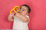 4 month old baby girl closeup on back holding toy rattle with small balls inside