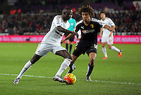 (L-R) Modou Barrow of Swansea is challenged by Nathan Ake of Watford during the Barclays Premier League match between Swansea City and Watford at the Liberty Stadium, Swansea on January 18 2016
