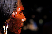 Para State, Brazil. Kayapo warrior from A-Ukre village with face paint and bead ear rings at Altamira.