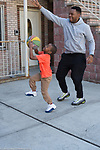 5 year old boy outside playing basketball with father