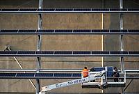 GERMANY Hamburg, IBA exhibition, an old war bunker is changed into an renewable energy project, installation of solar panels / DEUTSCHLAND  Hamburg, Energiebunker Wilhelmsburg , IBA Projekt, Energieerzeugung aus Solarenergie, Biogas, Holzhackschnitzeln und Abwaerme aus einem benachbarten Industriebetrieb, der Energiebunker soll einen Teil des Reiherstiegviertels mit Waerme versorgen und gleichzeitig erneuerbaren Strom in das Stromnetz einspeisen. Der Energiebunker soll circa 22.500 MWh Waerme und fast 3.000 MWh Strom erzeugen. Das entspricht dem Waermebedarf von circa 3.000 Haushalten und dem Strombedarf von etwa 1.000 Haushalten, Montage der Solon PV Module an der Suedseite des ehemaligen Flakbunkers mit Hebebühne