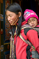A Bhutanese lady carrying a young child on her back at  Jakar, Bhutan