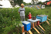 Ionel Farcas Cozmin, 54 years old, from Mures in Transylvania, with his grandson Catalin in front of the hives.
