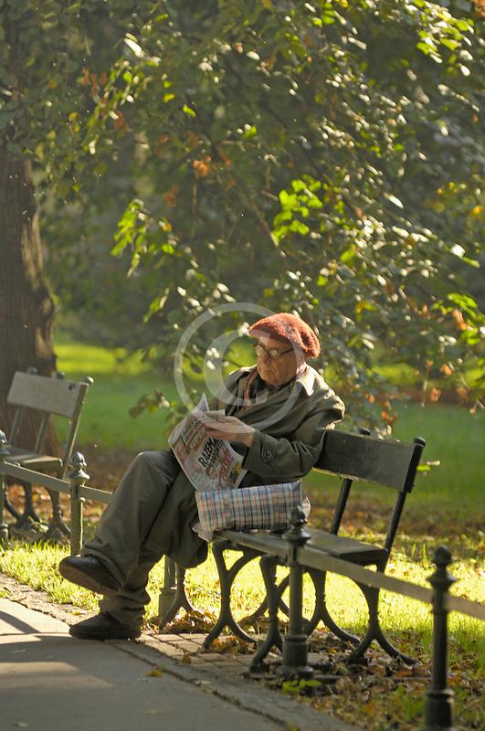 Poland, Krakow, Man reading newspaper on park bench