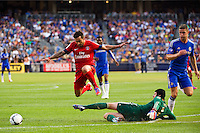 Ezequiel Lavezzi (11) of Paris Saint-Germain jumps over the tackle of Chelsea FC goalkeeper Petr Cech (1). Chelsea FC and Paris Saint-Germain played to a 1-1 tie during a 2012 Herbalife World Football Challenge match at Yankee Stadium in New York, NY, on July 22, 2012.