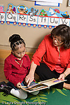 Education Preschool 3-5 year olds female teacher sitting on floor and reading to girl pointing at page vertical