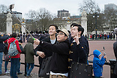 Tourists takes selfies with smartphone cameras at Buckingham Palace, London.
