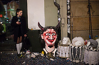 A woman stands against a wall next to instruments and masks used by participants in Fasnacht, the Carnival of Basel in Switzerland. Feb. 26, 2015.