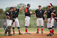 Edgewood Eagles head coach Al Brisack makes a pitching change as (clockwise) catcher Jacob Popp, third baseman Kyle Semrad (36), shortstop Ryan Fields (9), second baseman Max Orput and first baseman Dane Lamont look on during a game against the Babson Beavers on March 18, 2019 at Lee County Player Development Complex in Fort Myers, Florida.  Babson defeated Edgewood 23-7.  (Mike Janes/Four Seam Images)