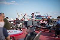 Menschen fahren bei sonnigem Fruehlingswetter im Hamburger Hafen auf einer Linien-Faehre der Hamburger Verkehrsbetriebe. Der Linenverkehr wird von vielen Menschen als guenstige Alternative fuer eine Hafenrundfahrt genutzt, die aufgrund der Corona-Einschraenkungen nicht stattfindet.<br /> Im Hintergund die Skyline von Hamburg.<br /> 9.5.2020, Hamburg<br /> Copyright: Christian-Ditsch.de<br /> [NUR FUER REDAKTIONELLE ZWECKE! Werbung nur auf Anfrage beim Fotografen.Inhaltsveraendernde Manipulation des Fotos nur nach ausdruecklicher Genehmigung des Fotografen. Vereinbarungen ueber Abtretung von Persoenlichkeitsrechten/Model Release der abgebildeten Person/Personen liegen nicht vor. NO MODEL RELEASE! Don't publish without copyright Christian-Ditsch.de, Veroeffentlichung nur mit Fotografennennung, sowie gegen Honorar, MwSt. und Beleg. Konto: I N G - D i B a, IBAN DE58500105175400192269, BIC INGDDEFFXXX, Kontakt: post@christian-ditsch.de<br /> Bei der Bearbeitung der Dateiinformationen darf die Urheberkennzeichnung in den EXIF- und  IPTC-Daten nicht entfernt werden, diese sind in digitalen Medien nach §95c UrhG rechtlich geschuetzt. Der Urhebervermerk wird gemaess §13 UrhG verlangt.]