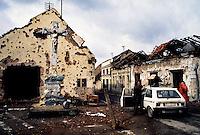 Vukovar / Croazia 11/1991 <br /> Importante centro industriale della Slavonia sulla riva del fiume Danubio. Vukovar è stata al centro della più aspra battaglia dell'intero conflitto balcanico per la definizione dei nuovi confini tra Serbia e Croazia. Nella fotografia alcuni profughi in fuga tra le case distrutte. Il 17 novembre 1991 quando Vukovar cade nelle mani delle milizie serbe è ridotta ad un cumulo di macerie.<br /> Important industrial center of Slavonia on the bank of the river Danube. Vukovar was at the center of the most severe battle of the entire conflict in the Balkans for the definition of new borders between Serbia and Croatia. In the photograph some refugees fleeing from the destroyed houses. On 17 November 1991, when Vukovar fell into the hands of the Serb militias is reduced to a pile of rubble. <br /> Photo Livio Senigalliesi