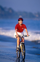Woman riding a bicycle on the beach.