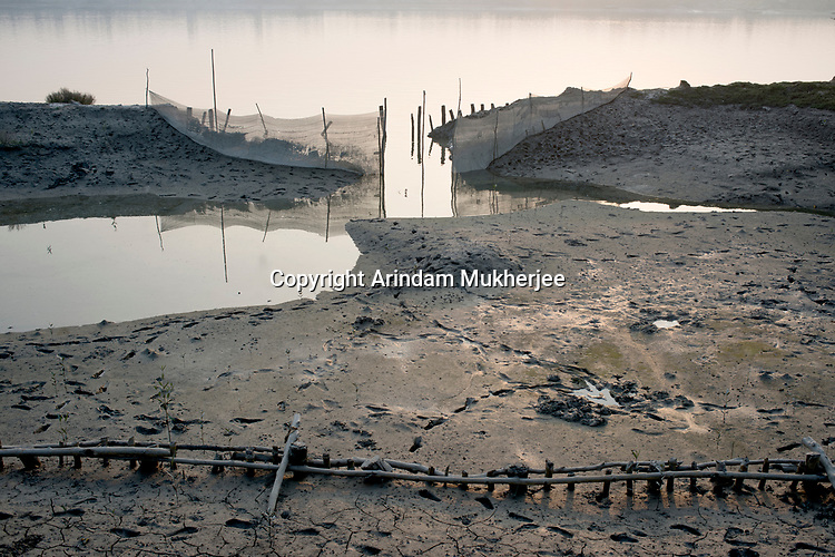 A ditch is created on the bank of a river during the low tide. Villagers put different kinds of net to catch fish which enters with high tide. Life in Sunderbans is vey much dependent on solar and lunar position along with high tide and low tide. Sunderbans, West Bengal, India. Arindam Mukherjee