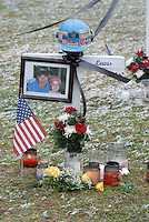 A miner's helmet sits atop the cross for Sago miner Dave Lewis at the memorial on the county courthouse lawn in Phillipi, WV Friday, Jan. 6, 2006. Lewis is one of the 12 miners killed in the Sago mine explosion. (Gary Gardiner/EyePush Newsphotos)<br />