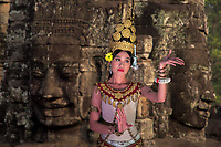 Beautiful Apsara dancer in front of Bayon Temple Buddha's face in the famous, ancient Khmer Angkor Wat temple, Siem Reap, Cambodia Southeast Asia