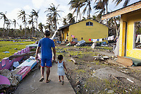Philippines. Province Eastern Samar. Hernani. Barangay (neighbourhood) Carmel. A father holding his daughter's hand walks among rubbles of the Children Elementary School which was destroyed by typhoon Haiyan's winds and storm surge. Typhoon Haiyan, known as Typhoon Yolanda in the Philippines, was an exceptionally powerful tropical cyclone that devastated the Philippines. Haiyan is also the strongest storm recorded at landfall in terms of wind speed. Typhoon Haiyan's casualties and destructions occured during a powerful storm surge, an offshore rise of water associated with a low pressure weather system. Storm surges are caused primarily by high winds pushing on the ocean's surface. The wind causes the water to pile up higher than the ordinary sea level. 24.11.13 © 2013 Didier Ruef