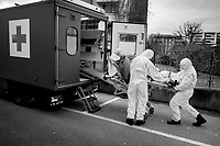 Due to the spread of the coronavirus (also called Covid-19) and given the increase in cases in Ticino, the Clinica Luganese Moncucco welcomes patients affected by the coronavirus. A military ambulance brings a coronavirus patient to the Clinica Luganese Moncucco which works as Covid-19 Hospital. A soldier opens the ambulance door while two nurses pulled down an emergency medical stretcher