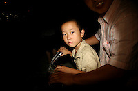 CHINA. Beijing. A young boy riding on his father's bike near the Olympic village during the Beijing 2008 Summer Olympics. 2008