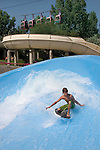 Young Caucasian male surfing on an artificial wave at a water park, Denver, Colorado. .  John offers private photo tours in Denver, Boulder and throughout Colorado. Year-round. .  John offers private photo tours in Denver, Boulder and throughout Colorado. Year-round.
