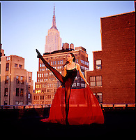 Dancer in red on roof with Empire State Building in background