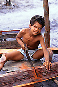 Porto Seguro, Bahia State, Brazil. Young Pataxo Indian boy sawing through a large piece of hardwood timber.