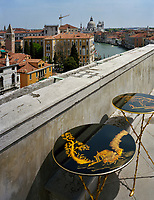Two vintage Fornasetti side tables are displayed on the roof terrace of Lars Rachen's Venetian apartment, which overlooks the Grand Canal and the Basilica di Santa Maria della Salute