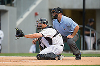Charlotte Knights catcher Kevan Smith (32) sets a target as home plate umpire Ben May looks over his shoulder during the game against the Norfolk Tides at BB&T BallPark on April 9, 2015 in Charlotte, North Carolina.  The Knights defeated the Tides 6-3.   (Brian Westerholt/Four Seam Images)