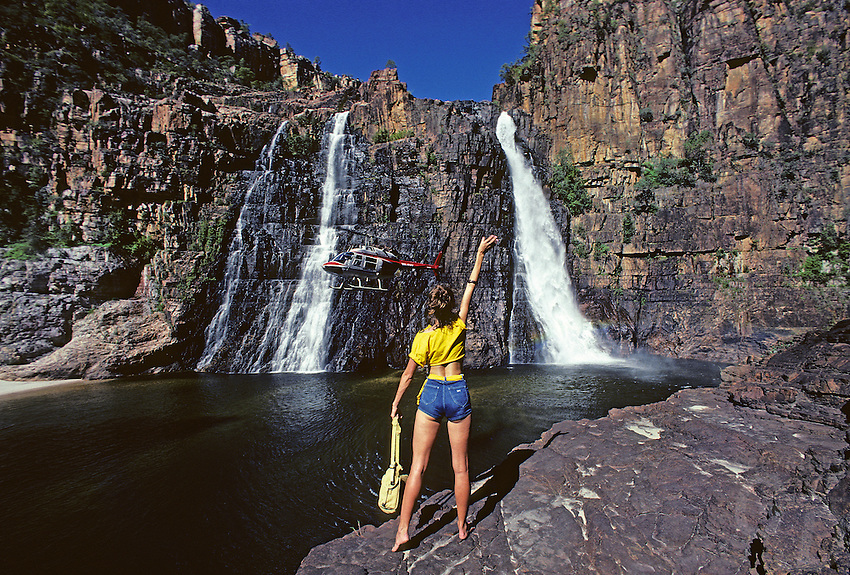 Girl at Twin Falls with a approaching Helicopter at the falls, Northern Territory, Australia