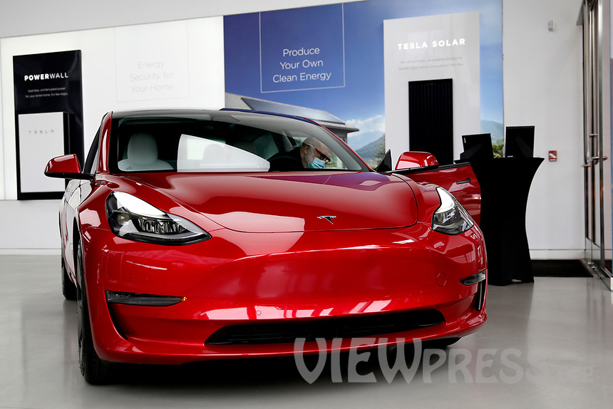 NEW YORK - NEW YORK - MARCH 24: A man sits on a Tesla car at its local store in Lower Manhattan on March 24, 2021 in New York. Tesla Inc said it bought $1.5 billion worth of bitcoin and would soon accept it as a form of payment for its cars. (Photo by John Smith/VIEWpress)